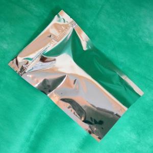 металлизированный дой-пак лежит на столе на зеленом сукне.