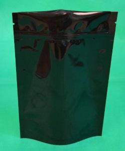 чёрный дой-пак лежит на столе на зеленом сукне.