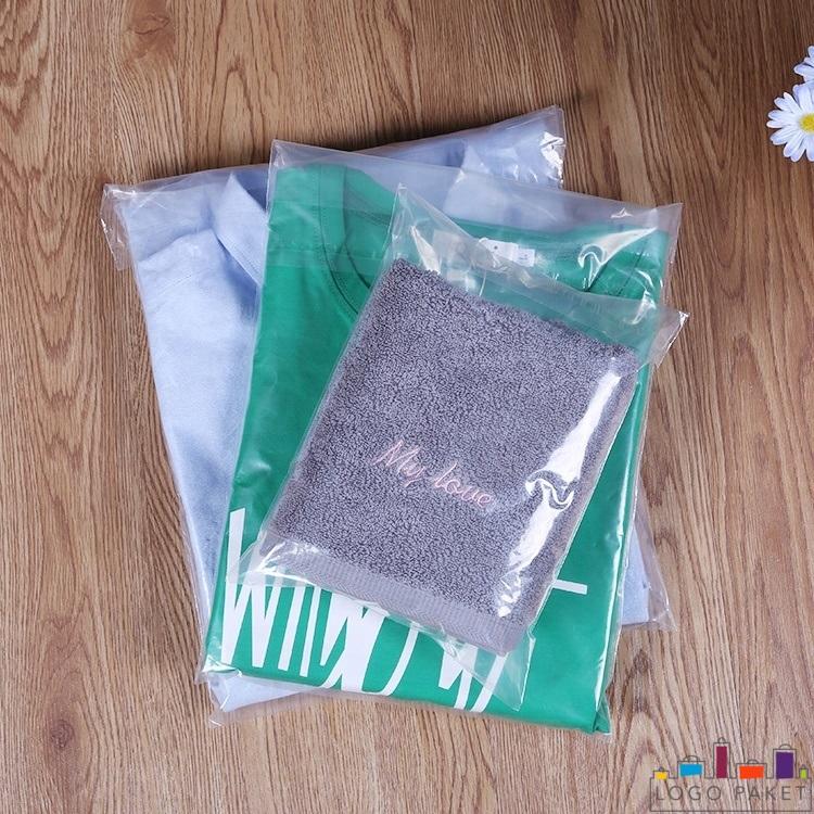сорочки в пакете для одежды лежат на деревянном столе.