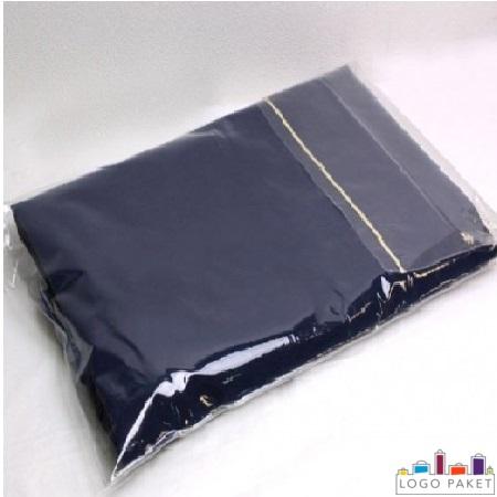 синие джинсы в пакете для одежды с клейким клапаном лежат на белом фоне.